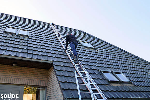 man op dak met ladder